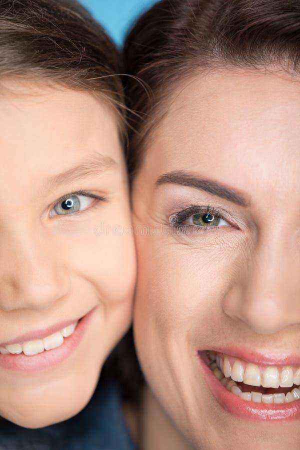 Ευτυχείς μητέρα και κόρη που αγκαλιάζουν στο στούντιο στο μπλε στοκ εικόνα με δικαίωμα ελεύθερης χρήσης