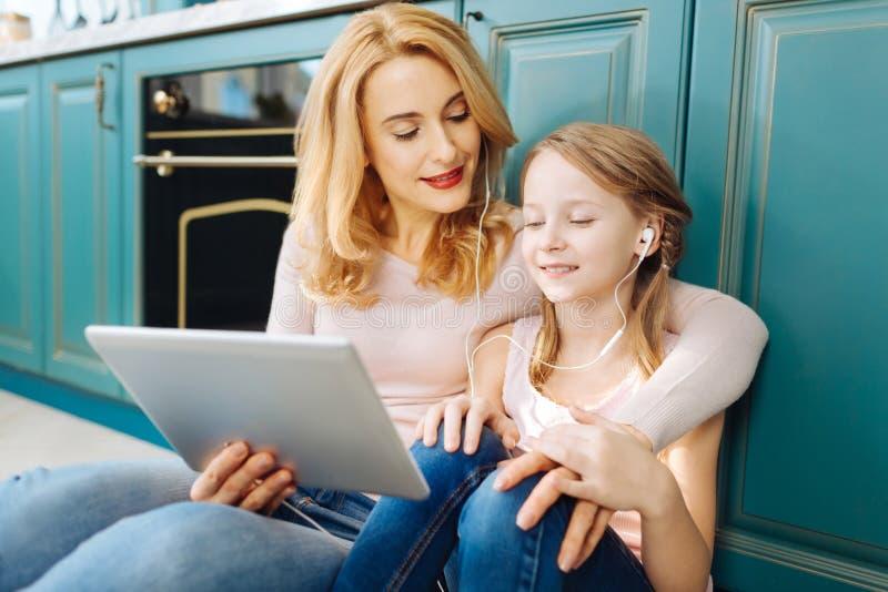 Ευτυχείς μητέρα και κόρη που ακούνε τη μουσική στοκ εικόνες
