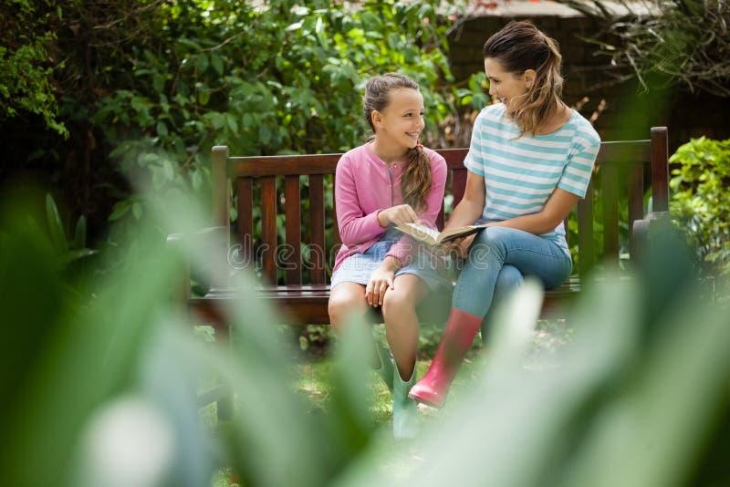Ευτυχείς μητέρα και κόρη που εξετάζουν η μια την άλλη καθμένος με το μυθιστόρημα στον πάγκο στοκ φωτογραφία