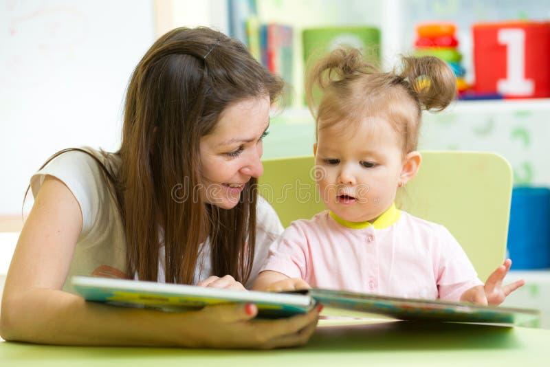 Ευτυχείς μητέρα και κόρη που διαβάζουν ένα βιβλίο από κοινού στοκ φωτογραφία με δικαίωμα ελεύθερης χρήσης