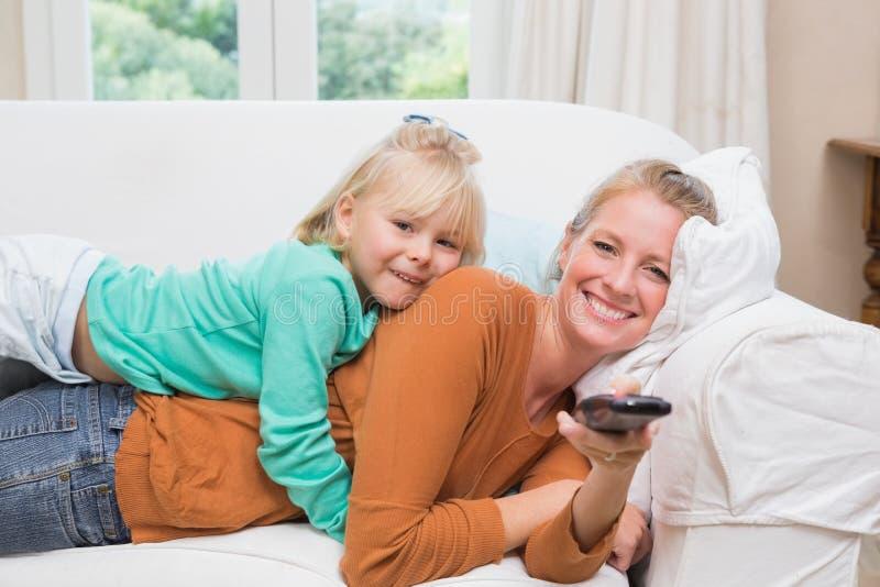 Ευτυχείς μητέρα και κόρη που προσέχουν τη TV στοκ εικόνες
