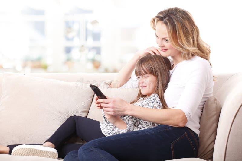 Ευτυχείς μητέρα και κόρη που προσέχουν τη TV στοκ φωτογραφία με δικαίωμα ελεύθερης χρήσης