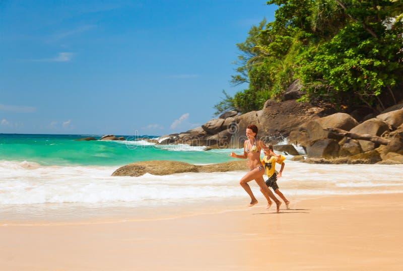 Ευτυχείς μητέρα και κόρη που τρέχουν στην παραλία στοκ εικόνες