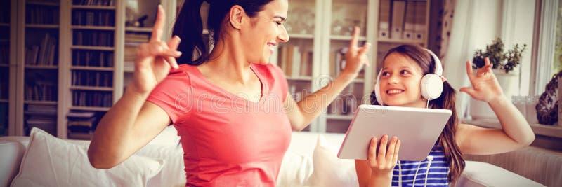 Ευτυχείς μητέρα και κόρη που χρησιμοποιούν την ψηφιακή ταμπλέτα και το χορό στοκ εικόνα