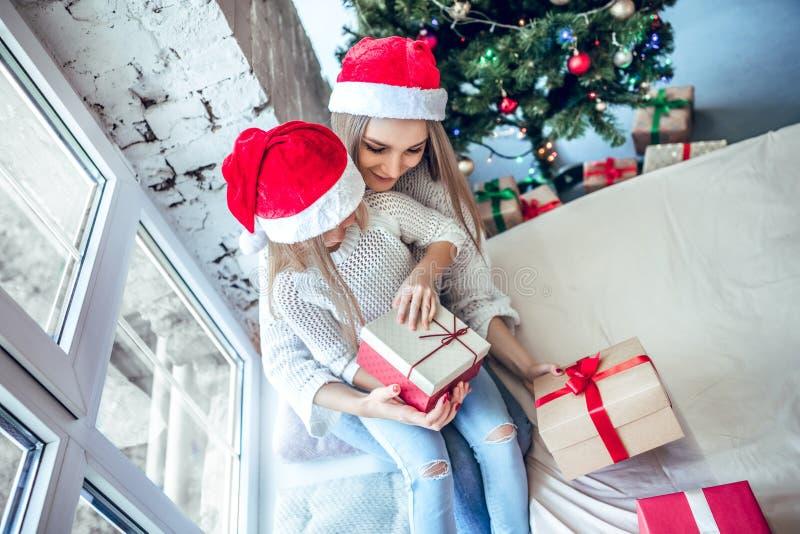 Ευτυχείς μητέρα και κόρη στα καπέλα santa με το κιβώτιο δώρων πέρα από το δωμάτιο με το υπόβαθρο χριστουγεννιάτικων δέντρων στοκ φωτογραφία