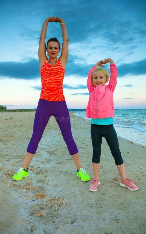 Ευτυχείς μητέρα και κόρη seacoast στο τέντωμα βραδιού στοκ φωτογραφία