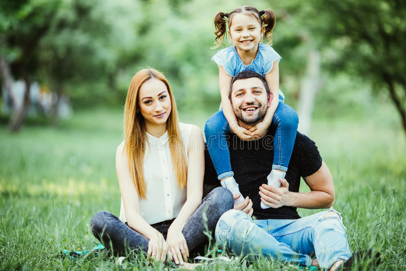 Ευτυχείς μητέρα, πατέρας και κόρη στο πάρκο Σκηνή φύσης ομορφιάς με τον οικογενειακό υπαίθριο τρόπο ζωής Ευτυχής κόρη στην πλάτη  στοκ εικόνες