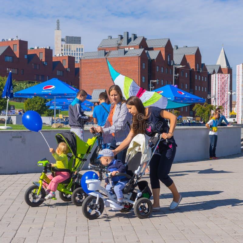 Ευτυχείς μητέρες με τα παιδιά στη μεταφορά μωρών που περπατούν στο κεντρικό πάρκο κατά τη διάρκεια της τοπικής δραστηριότητας ημέ στοκ φωτογραφία