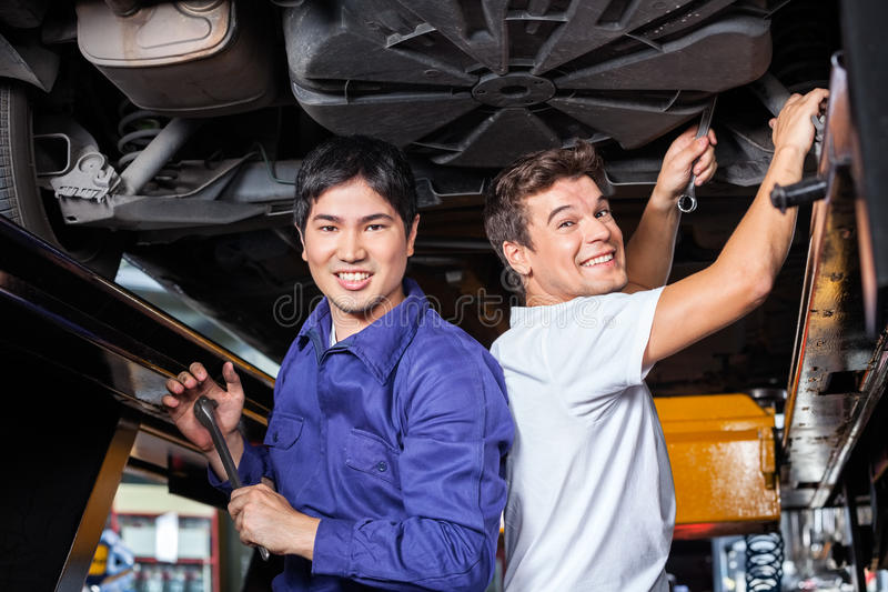 Ευτυχείς μηχανικοί που εργάζονται κάτω από το ανυψωμένο αυτοκίνητο στοκ φωτογραφία με δικαίωμα ελεύθερης χρήσης