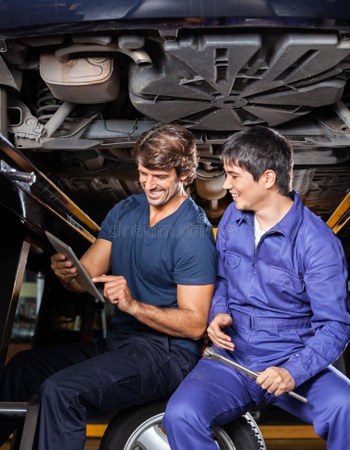 Ευτυχείς μηχανικοί που χρησιμοποιούν την ψηφιακή ταμπλέτα κάτω από το αυτοκίνητο στοκ φωτογραφία με δικαίωμα ελεύθερης χρήσης