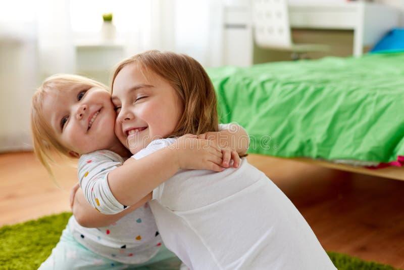 Ευτυχείς μικρά κορίτσια ή αδελφές που αγκαλιάζουν στο σπίτι στοκ φωτογραφίες με δικαίωμα ελεύθερης χρήσης