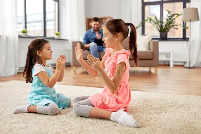 Ευτυχείς μικρές αδελφές που παίζουν χτυπώντας το παιχνίδι στο σπίτι στοκ εικόνες