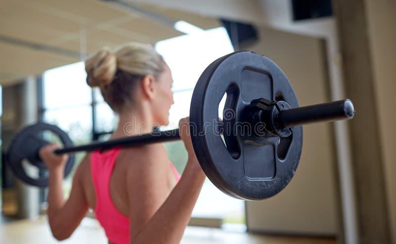Ευτυχείς μυ'ες κάμψης γυναικών με το barbell στη γυμναστική στοκ φωτογραφία με δικαίωμα ελεύθερης χρήσης