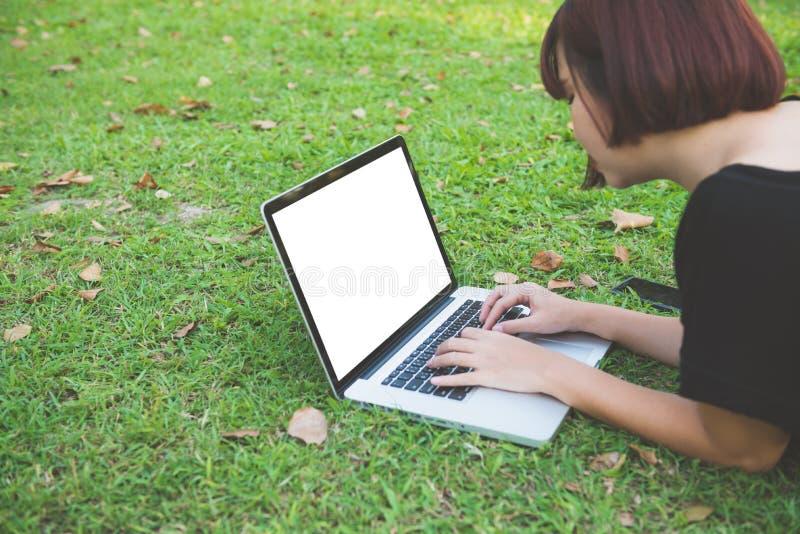 Ευτυχείς νέες ασιατικές γυναίκες hipster που εργάζονται στο lap-top στο πάρκο Έννοιες τρόπου ζωής και τεχνολογίας στοκ εικόνες