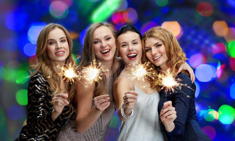 Ευτυχείς νέες γυναίκες με τα sparklers πέρα από τα φω'τα στοκ εικόνες