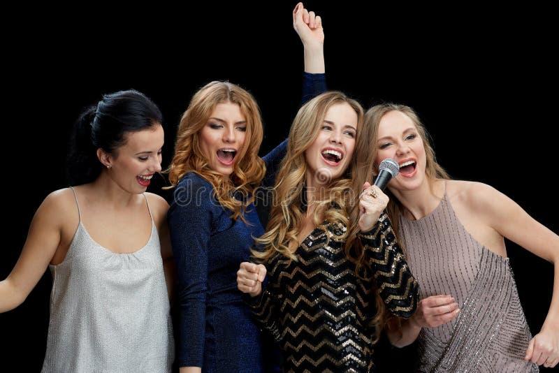 Ευτυχείς νέες γυναίκες με το καραόκε τραγουδιού μικροφώνων στοκ φωτογραφία με δικαίωμα ελεύθερης χρήσης