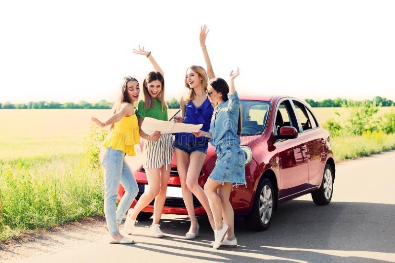 Ευτυχείς νέες γυναίκες με το χάρτη που στέκεται κοντά στο αυτοκίνητο στην επαρχία στοκ εικόνες