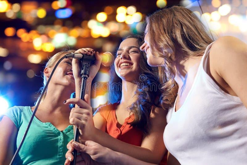 Ευτυχείς νέες γυναίκες που τραγουδούν το καραόκε στη λέσχη νύχτας στοκ εικόνα