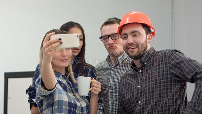 Ευτυχείς νέοι αρχιτέκτονες που παίρνουν τα αστεία selfies στην αρχή στοκ εικόνα