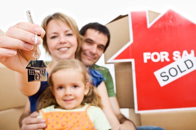Ευτυχείς νέοι ιδιοκτήτες σπιτιού - οικογενειακή κινούμενη έννοια στοκ φωτογραφίες με δικαίωμα ελεύθερης χρήσης
