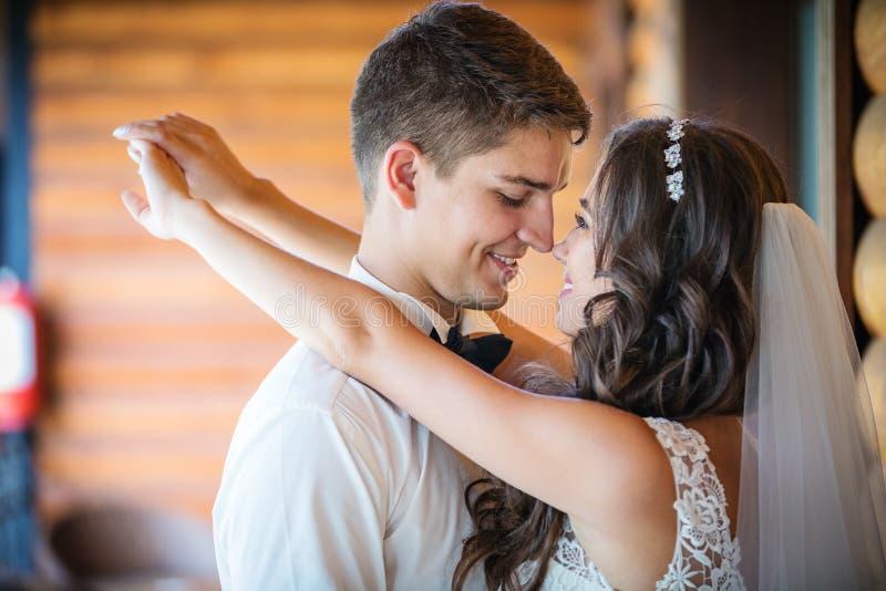Ευτυχείς νέοι νύφη και νεόνυμφος που πηγαίνουν να φιλήσει στοκ εικόνες