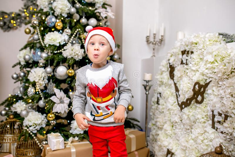 Ευτυχείς νέοι οικογένεια, πατέρας, μητέρα και γιος, το βράδυ Χριστουγέννων στο σπίτι Ένα μικρό αγόρι στη στάση καπέλων Santa κοντ στοκ φωτογραφίες