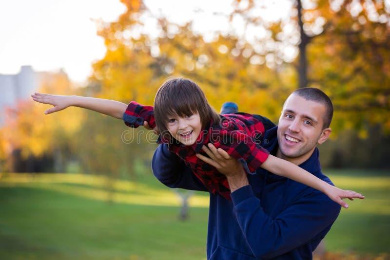 Ευτυχείς νέοι πατέρας και παιδί που έχουν τη διασκέδαση υπαίθρια στο πάρκο στοκ φωτογραφίες με δικαίωμα ελεύθερης χρήσης