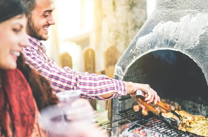 Ευτυχείς νέοι φίλοι που κάνουν ένα κόμμα σχαρών που ψήνει το κρέας στο κατώφλι στη σχάρα - όμορφο άτομο που μαγειρεύει το ψημένο  στοκ εικόνες