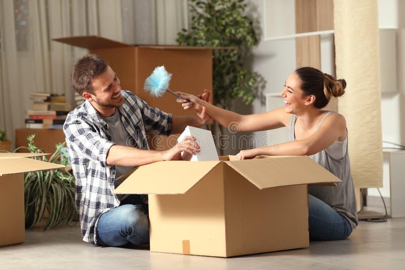 Ευτυχείς να αστειευτεί ζευγών unboxing περιουσίες που κινούνται κατ' οίκον στοκ εικόνες