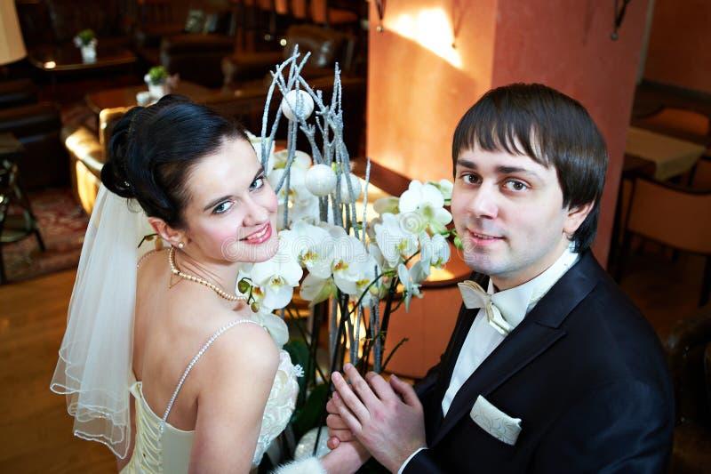 Ευτυχείς νύφη και νεόνυμφος κοντά στα λουλούδια στοκ εικόνες