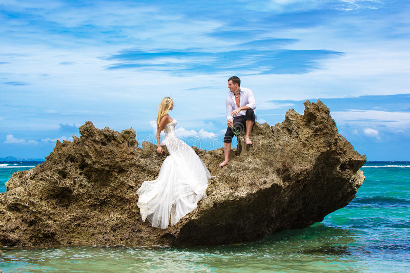 Ευτυχείς νύφη και νεόνυμφος που έχουν τη διασκέδαση σε μια τροπική παραλία κάτω από το π στοκ εικόνες