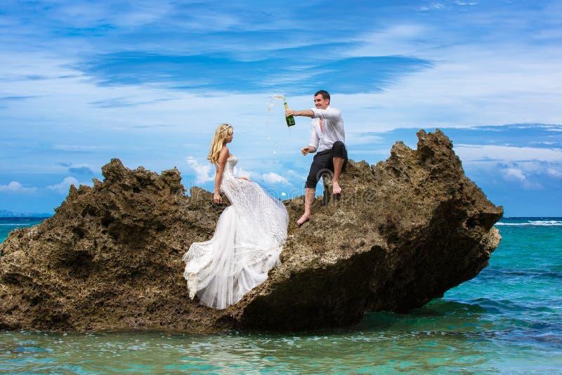 Ευτυχείς νύφη και νεόνυμφος που έχουν τη διασκέδαση σε μια τροπική παραλία κάτω από το π στοκ φωτογραφία