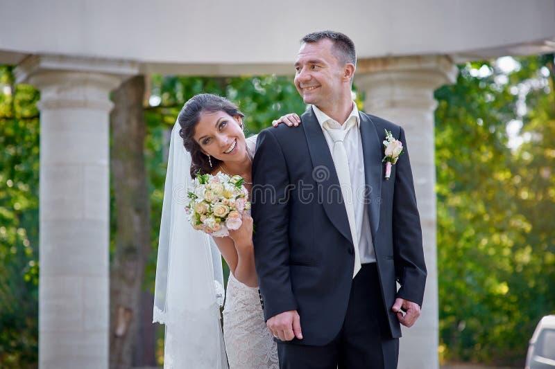 Ευτυχείς νύφη και νεόνυμφος που περπατούν μεταξύ των στηλών στοκ φωτογραφία με δικαίωμα ελεύθερης χρήσης