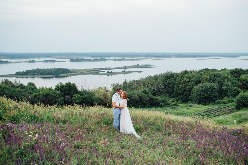 Ευτυχείς νύφη και νεόνυμφος που περπατούν στην πράσινη χλόη στοκ φωτογραφία με δικαίωμα ελεύθερης χρήσης