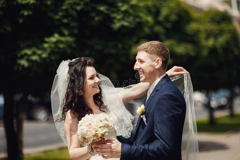 Ευτυχείς νύφη και νεόνυμφος στην ηλιόλουστη αλέα πόλεων στο γαμήλιο περίπατο στοκ φωτογραφία με δικαίωμα ελεύθερης χρήσης
