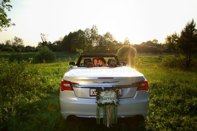 Ευτυχείς νύφη και νεόνυμφος στο καμπριολέ στοκ εικόνες