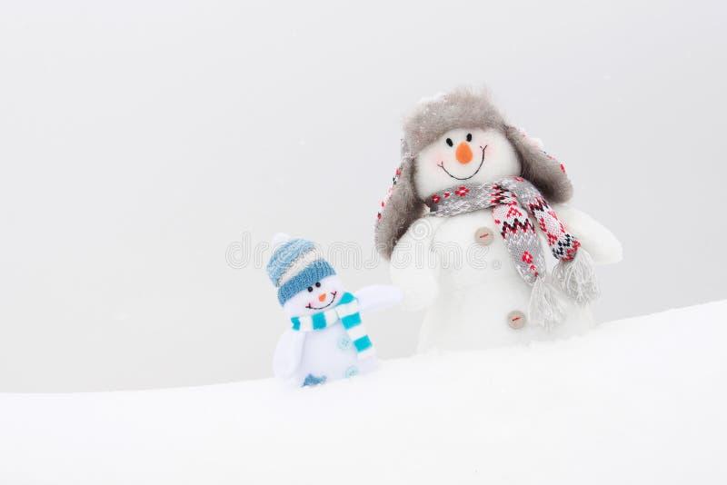 Ευτυχείς οικογένεια ή φίλοι χειμερινών χιονανθρώπων στοκ εικόνα με δικαίωμα ελεύθερης χρήσης