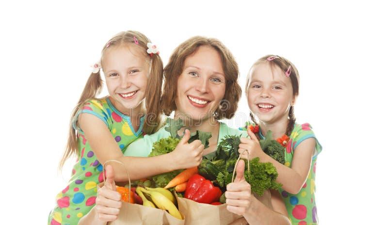 Ευτυχείς οικογενειακές μητέρα και κόρες με τις τσάντες των λαχανικών στοκ εικόνες