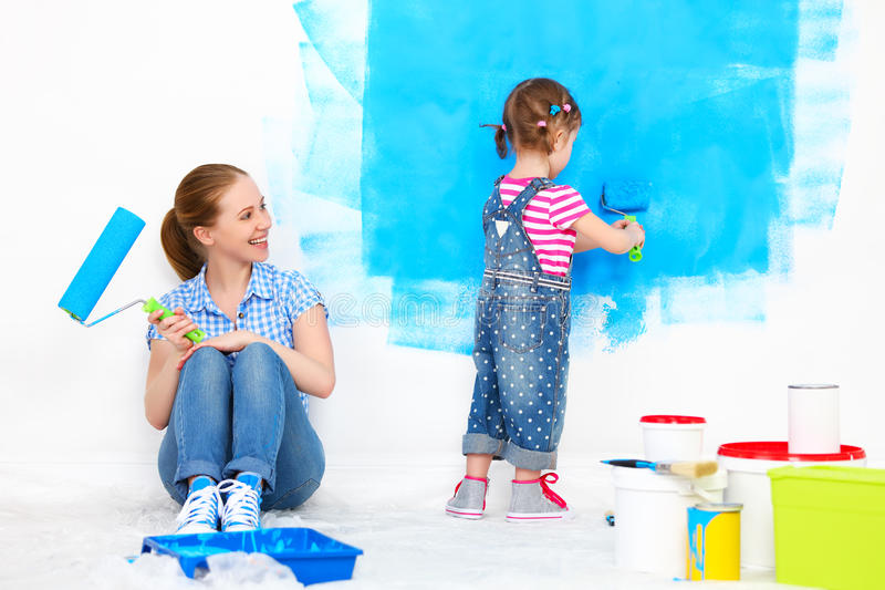 Ευτυχείς οικογενειακή μητέρα και κόρη παιδιών που κάνει τις επισκευές, χρώμα wal στοκ εικόνα με δικαίωμα ελεύθερης χρήσης