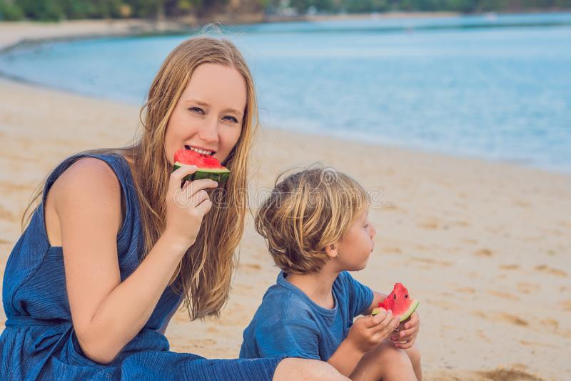 Ευτυχείς οικογενειακοί μητέρα και γιος που τρώνε ένα καρπούζι στην παραλία Τα παιδιά τρώνε τα υγιή τρόφιμα στοκ εικόνα