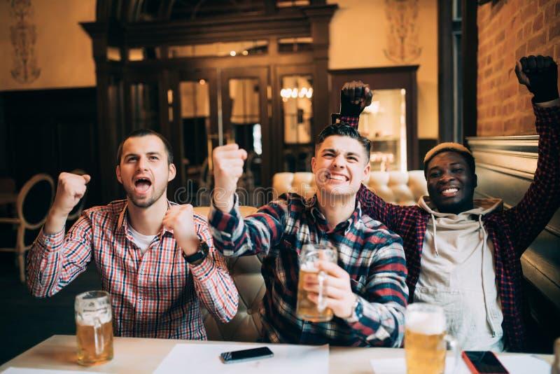 Ευτυχείς οπαδοί ποδοσφαίρου ή αρσενικοί φίλοι που πίνουν την μπύρα και που γιορτάζουν τη νίκη της καλύτερης ομάδας ή εθνική ομάδα στοκ φωτογραφία