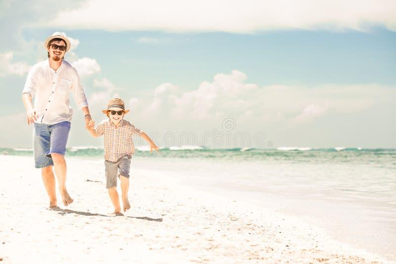 Ευτυχείς πατέρας και γιος που απολαμβάνουν το χρόνο παραλιών στο καλοκαίρι στοκ εικόνα