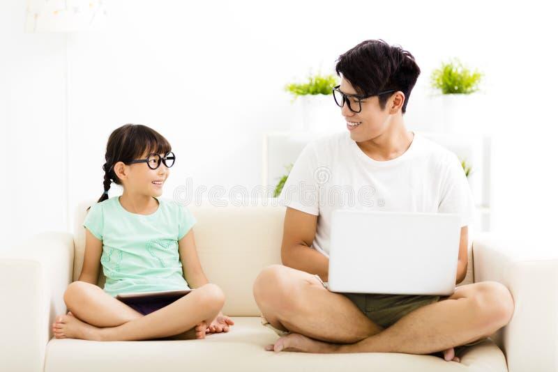 Ευτυχείς πατέρας και κόρη που χρησιμοποιούν το lap-top στοκ εικόνες