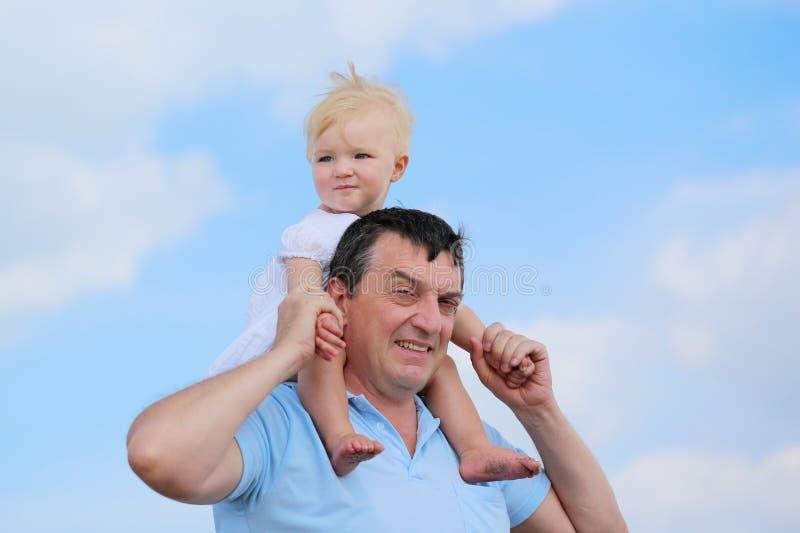 Ευτυχείς πατέρας και κόρη υπαίθρια ενάντια στο μπλε ουρανό στοκ εικόνα