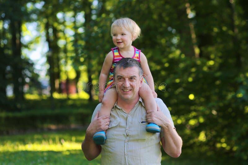 Ευτυχείς πατέρας και κόρη υπαίθρια στο πάρκο στοκ φωτογραφία