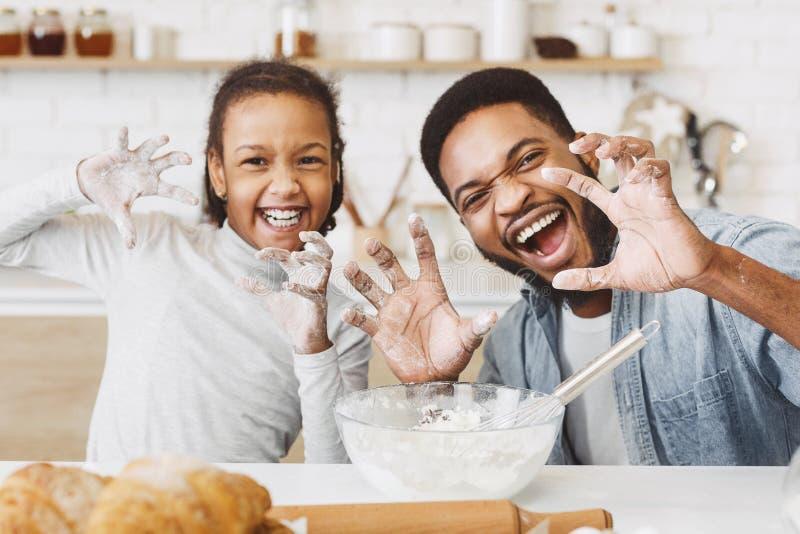 Ευτυχείς πατέρας και κόρη afro στην κουζίνα στοκ εικόνα