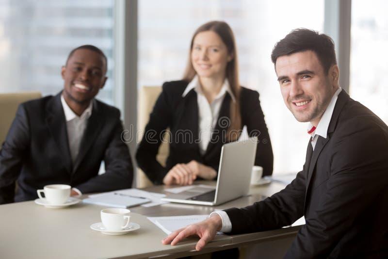 Ευτυχείς πολυεθνικοί εργαζόμενοι γραφείων που θέτουν στο γραφείο στοκ εικόνα