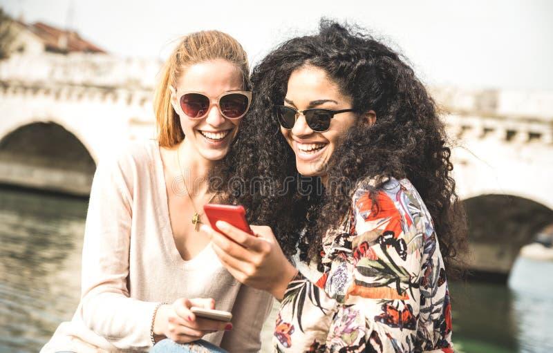 Ευτυχείς πολυφυλετικές φίλες που έχουν τα outddors διασκέδασης με το κινητό τηλέφωνο στοκ φωτογραφία