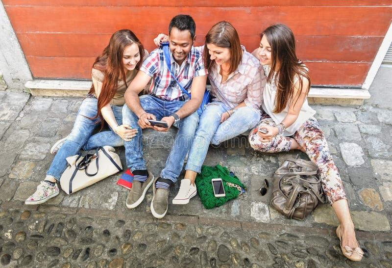 Ευτυχείς πολυφυλετικοί καλύτεροι φίλοι που έχουν τη διασκέδαση που χρησιμοποιεί το κινητό έξυπνο τηλέφωνο στοκ εικόνα με δικαίωμα ελεύθερης χρήσης