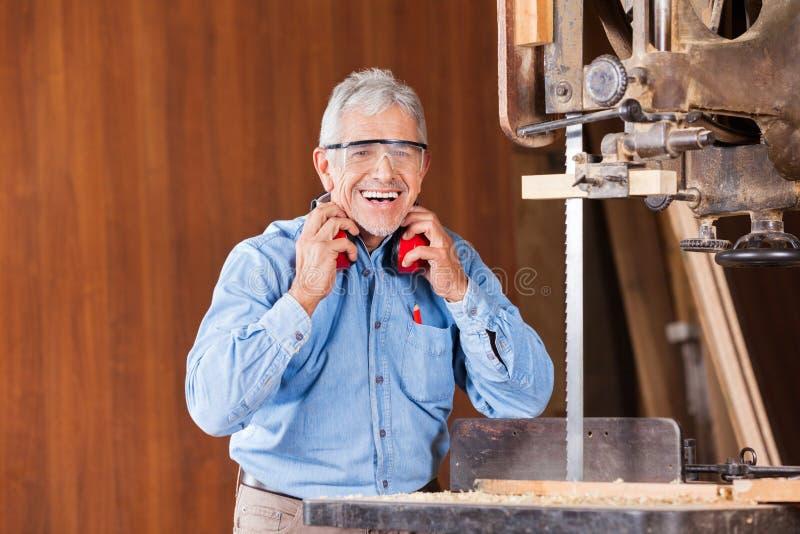 Ευτυχείς προστάτες αυτιών εκμετάλλευσης ξυλουργών από την πριονοκορδέλλα στοκ εικόνες με δικαίωμα ελεύθερης χρήσης